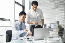 Chinese businessmen discussing work in office — Stock Photo