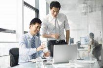 Hommes d'affaires chinois discutant de travail au bureau — Photo de stock