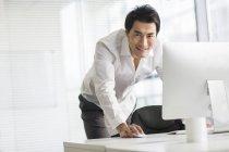 Empresário chinês usando o computador no escritório e olhando na câmera — Fotografia de Stock