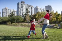 Chinese mother and daughter holding hands and spinning in park — Stock Photo