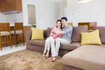 Couple chinois regardant la télévision sur le canapé dans le salon — Photo de stock