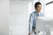 Китайский бизнесмен стоит за компьютером в офисе и смотрит в сторону — стоковое фото