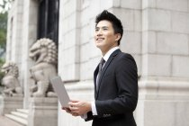 Chinese businessman with laptop in front of building — Stock Photo