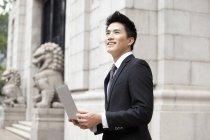Empresário chinês com laptop na frente do edifício — Fotografia de Stock