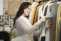 Mulher chinesa escolhendo roupas em boutique — Fotografia de Stock