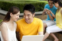 Chinese using laptop in park with people in background — Stock Photo