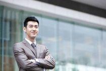 Retrato de empresário chinês com armas cruzadas em frente ao prédio de negócios — Fotografia de Stock