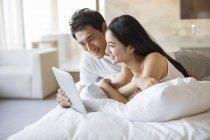 Casal chinês usando tablet digital na cama — Fotografia de Stock