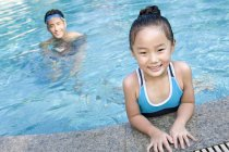 Chinese father and daughter swimming in pool — Stock Photo