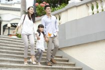 Chinese family walking down steps in city — Stock Photo