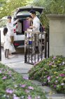 Famiglia cinese prendendo le borse della spesa dal bagagliaio — Foto stock