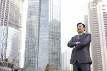 Chinese businessman standing with arms crossed in financial district — Stock Photo