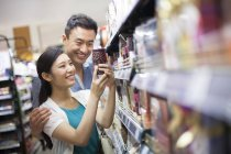 Chinese couple choosing goods in supermarket — Stock Photo