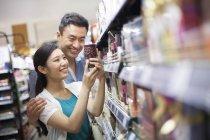 Китайская пара выбирает товары в супермаркете — стоковое фото