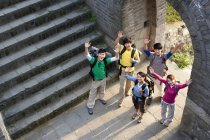 Group of Chinese backpackers waving on Great Wall — Stock Photo