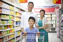 Chinese parents with son shopping in supermarket — Stock Photo