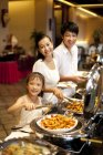 Chinese parents with daughter taking food at buffet — Stock Photo