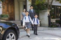 Китайські діти, тримаючись за руки і ходьба при батьками дивляться у фоновому режимі — стокове фото