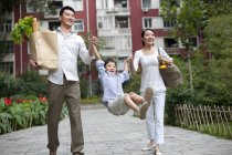 Chinese family with swinging son walking on street with groceries — Stock Photo