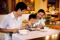 Chinese parents with son dining in restaurant — Stock Photo