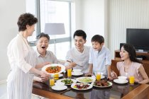 Chinese grandmother serving dinner for happy family — Stock Photo