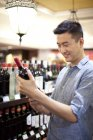 Chinese man choosing wine in supermarket — Stock Photo