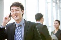Chinesischer Unternehmer spricht am Telefon mit Kolleginnen und Kollegen im Hintergrund drinnen — Stockfoto