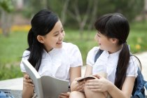 Schoolgirls sitting on steps, talking and reading books — Stock Photo