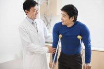 Médico chinês, ajudando o paciente com muletas — Fotografia de Stock