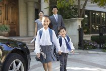 Chinese children holding hands and walking while parents watching in background — Stock Photo