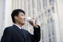 Chinese businessman drinking coffee on street — Stock Photo