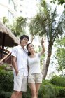Chinese couple pointing at view on vacation — Stock Photo