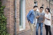 Китайская команда бизнесменов беседует с цифровым планшетом в городе — стоковое фото