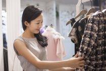 Mulher asiática escolhendo roupas em boutique — Fotografia de Stock