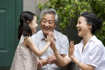 Chinese elementary age girl playing with grandparents on street — Stock Photo