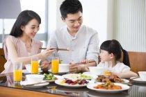 Famille chinoise avec la jeune fille en train de déjeuner — Photo de stock