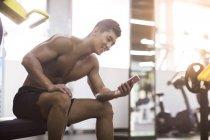 Chinese benutzt Smartphone im Fitnessstudio — Stockfoto