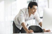 Empresário chinês de pé e usando computador no escritório — Fotografia de Stock