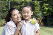 Chinesischen Mutter und Tochter posiert auf Tennisplatz — Stockfoto