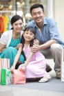 Chinese parents and daughter posing with shopping bags in mall — Stock Photo