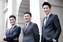 Chinese business team standing in front of building — Stock Photo