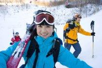 Femme chinoise avec des hommes à la station de ski de randonnée — Photo de stock