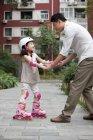 Pai chinês ajudando filha andar de patins — Fotografia de Stock