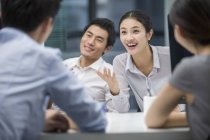 Chinese business people talking in office — Stock Photo