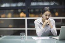 Китайская деловая женщина, сидящая с руками, сжатыми за столом в офисе — стоковое фото