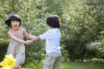 Enfants chinois tenant par la main et tourbillonnant dans jardin — Photo de stock