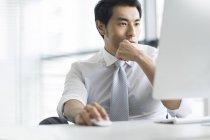 Empresário chinês usando computador na mesa de escritório — Fotografia de Stock
