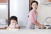 Chinos madre e hija lavar los platos en la cocina - foto de stock