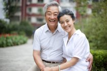 Senior Chinese couple sitting in park and holding hands — Stock Photo