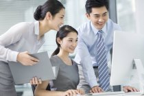 Chinese business people using computer in office — Stock Photo